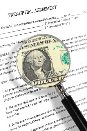 Prenuptial agreement with US dollar bill under magnifying glass.