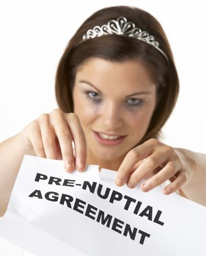 Woman tearing up prenuptial agreement contract.